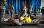 Second Place | General  NewsAndrew Craft, The Fayetteville ObserverLt. Col. Michelle Tirado prepares Sr. Airmen Robert Williams for transport to a C-130 during a mass casualty exercise at Pope Army Airfield.Comments : Quiet moment and nice juxtaposition of colors