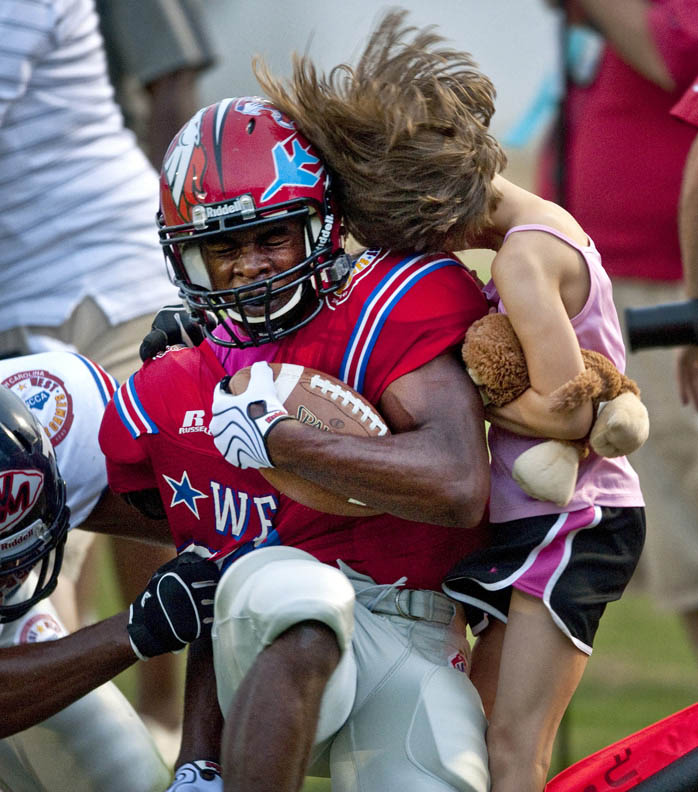 First Place | SportsLauren Carroll, Winston Salem JournelBallcarrier Sha'Quann Johnson is pushed out of bounds and collides with Jasper Duke, 9, who was standing on the sidelines and was unharmed.