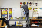 First Place | News Photo StoryErin Brethauer, The Asheville Citizen-TimesMaintenance worker Roger Richardson helps take down educational posters from the walls of teacher Regina Woody's walls on the last day of school at Buladean Elementary Tuesday.