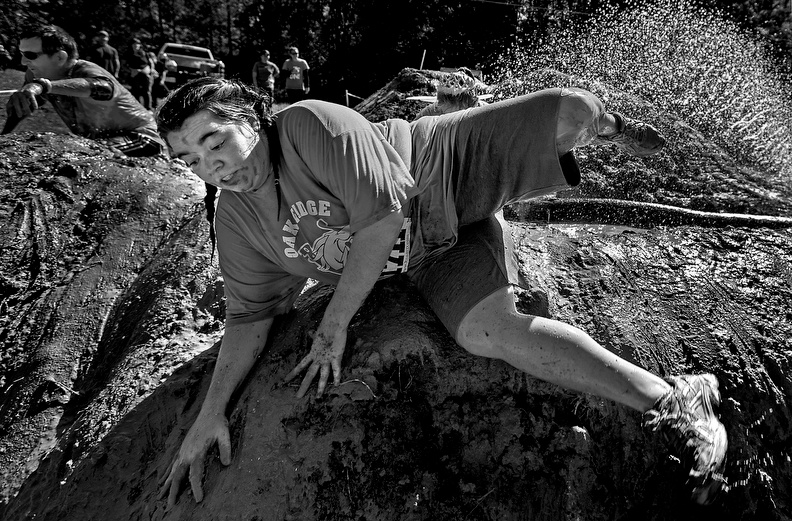 Sports POY: Runner UpJerry Wolford, News-RecordAnne Kriegel climbs over a mud wall after navigating a muddy water pit during the 2012 MudBug Run.