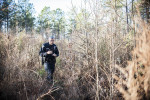 Third Place | Multiple PhotosMelissa Melvin-Rodriguez, The Fayetteville ObserverOfficer Alan Sanford treks through high brush in a wood line behind Lowe's on Skibo Road as he searches for homeless people during the Point in Time homeless count in Fayetteville and Cumberland County on Thursday, January 31, 2013.