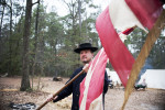 Second Place | Multiple PhotosMelissa Melvin-Rodriguez, The Fayetteville ObserverBrian Lee takes down a tattered American flag at the campsite of the Union soldiers during Bentonville's 148th anniversary program, {quote}One Continuous Fire of Destruction{quote} at the Bentonville Battlefield State Historic Site.