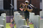 Third Place | General NewsChris Seward, The News and ObserverWebelos Scout Wyatt Murray, 9, with Troop 365, hustles to bring more flags to troop members as they place small American flags at the gravesites at Raleigh National Cemetery for Memorial Day on May 24, 2013.  `