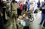 Third Place | General  NewsJames Robinson, The Fayetteville ObserverStaff Sgt. Allison Fields hugs her sons Liam, 2, left and Colin 4, right after returning home from Afghanistan Monday afternoon at Pope Field.