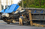 Third Place | Spot NewsCindy Burnham, The Fayetteville ObserverJudges Comments: Third place is fun image that wouldn't be the same without the driver. We only wish the caption would have included his name or some more information. Driver of the truck  gets a closer look at the undercarriage .The rig overturned on the Cliffdale Road bridge, landed on its side and spilled its load of wood into the road. The eastbound lanes, heading toward Fayetteville, of Cliffdale Road are closed from the All American Freeway exit ramp to McPherson Church Road. The wreck happened about 7:20 a.m.Thursday10/3/13
