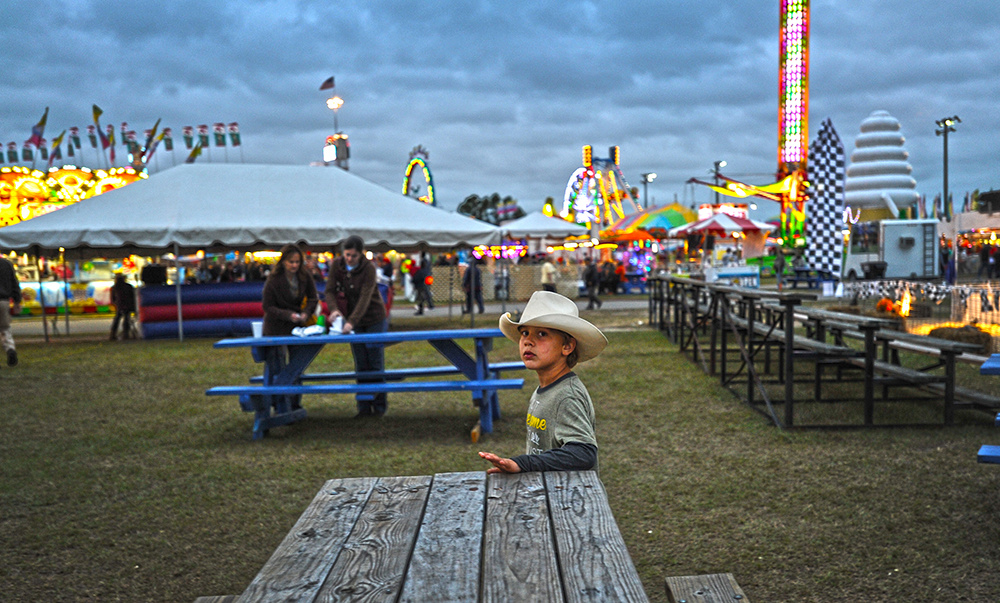 Honorable Mention I FeatureCindy Burnham, The Fayetteville ObserverJudges Comments: This honorable mention almost felt like it belonged in the portrait category. It has a nice overall feel and almost an eerie stillness. It could use a slight tighter crop or a closer shooting position. Logan Locklear waits for his father to bring him dinner at the Robeson County Fair.