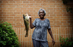 Third Place | PortraitJames Robinson, The Fayetteville ObserverJudges Comments: Third place is a quirky frame that gets you to connect with the subject quickly, but the brick background does not add anything to the image. Doris Gilmore with the 12lb Large Mouth Bass that she caught using a worm from a small pond in Coats NC.
