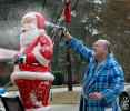 Second Place  | FeatureMark Dolejs, Daily DispatchThere is so much oddity here. It's December and the guy is cleaning a lawn ornament in his bathrobe. The expression on the Santa's face looks like a natural raction someone would have if they were being sprayed by a water hose. This is so surreal, yet here's the proof that it exists in North Carolina. Allen Short decided that Santa needed a good cleaning and a fresh coat of red paint. In preparation for the new paint, Short scrubbed and rinsed off the 25-year-old plastic Santa at his Oxford Road home.