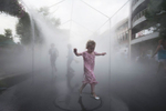 Honorable Mention | Feature Dillon  Deaton, Randolph Community CollegeA young girl runs through a mist tent at the Bele Chere Festival in Asheville,NC. {quote}Cooling off{quote}