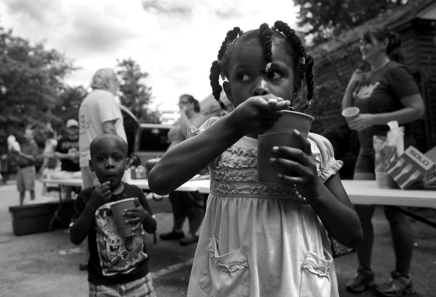 First Place | News Photo Story Travis Long, The News & ObserverChildren eat fruit from cups Sunday as the HumanBeans charity group distributed food to those in need in the parking lot of Mo's Diner near Moore's Square in downtown Raleigh. Police have started enforcing a city ordinance to stop volunteer and church groups from feeding the homeless in downtown Raleigh's Moore Square park.
