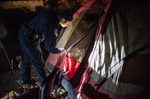 Third Place | News Photo Story Melissa Melvin-RodriguezOfficer Stacy Sanders takes a look inside a tent underneath the Person Street bridge during the Point in Time homeless count in Fayetteville and Cumberland County on Thursday, January 31, 2013.