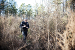 Third Place | News Photo Story Melissa Melvin-RodriguezOfficer Alan Sanford treks through high brush in a wood line behind Lowe's on Skibo Road as he searches for homeless people during the Point in Time homeless count in Fayetteville and Cumberland County on Thursday, January 31, 2013.