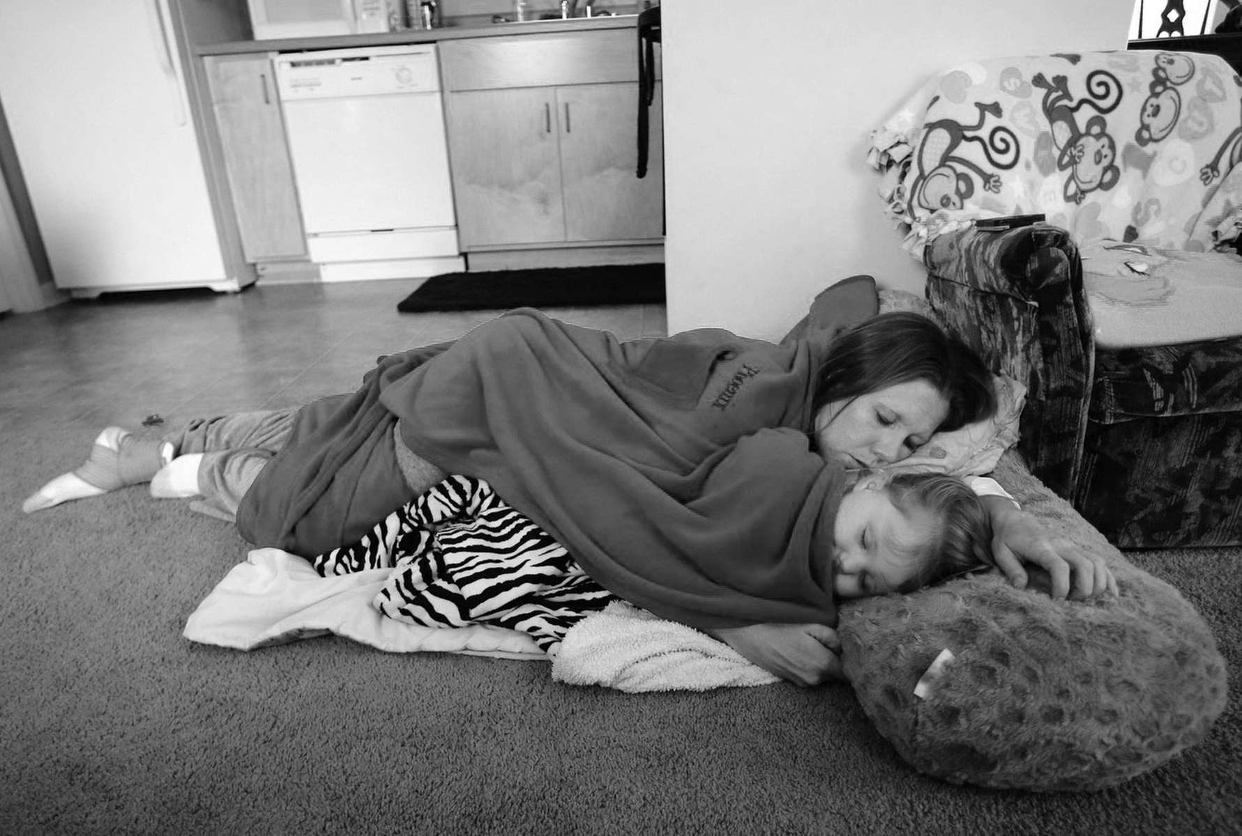 Honorable Mention | News Photo Story Al Drago, Elon UniversityShelly Shrum sleeps with her daughter, Phoenix, 2, on the living room floor after watching {quote}Barney & Friends{quote} in their home on the Cedar Street property of the Daniel Pitino Shelter that works with homeless women and families.