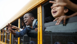 First Place | Feature Photo Story Jerry Wolford, News & RecordFourth grade student, Fael Mankasi, screams from his bus window as the bus pulls away.