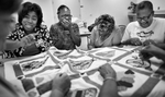 Honorable Mention | Feature Photo Story Jerry Wolford, News & Record(L to R) Teania Jackson (Smith Senior Center Director), Loretta McQueen, Betty Matthews and Gwen White laugh and cut up as they work in the final stages of their quilt.