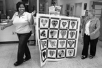 Honorable Mention | Feature Photo Story Jerry Wolford, News & RecordAs Gwen White (background) {quote}trumpets{quote} the quilt processional, Teania Jackson and June Callaghan proudly parade the quilt to its hanging place.