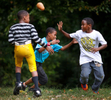 Third Place | Sports Photo Story Jerry Wolford, News & RecordWesley Harris (left), 8, Kenaya James (center), 10, and Mason Noil (right), 8, play football in the front yard of Wesley's house on Dillard St.