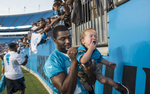 Third Place | Sports Feature Melissa Melvin-RodriguezCarolina Panthers wide receiver De\'Andre Presley signs his autograph on a crying Brewster Hogue, 20 months, following the team\'s first practice of training camp on Friday, July 25, 2014 at Bank of America Stadium in Charlotte, NC.