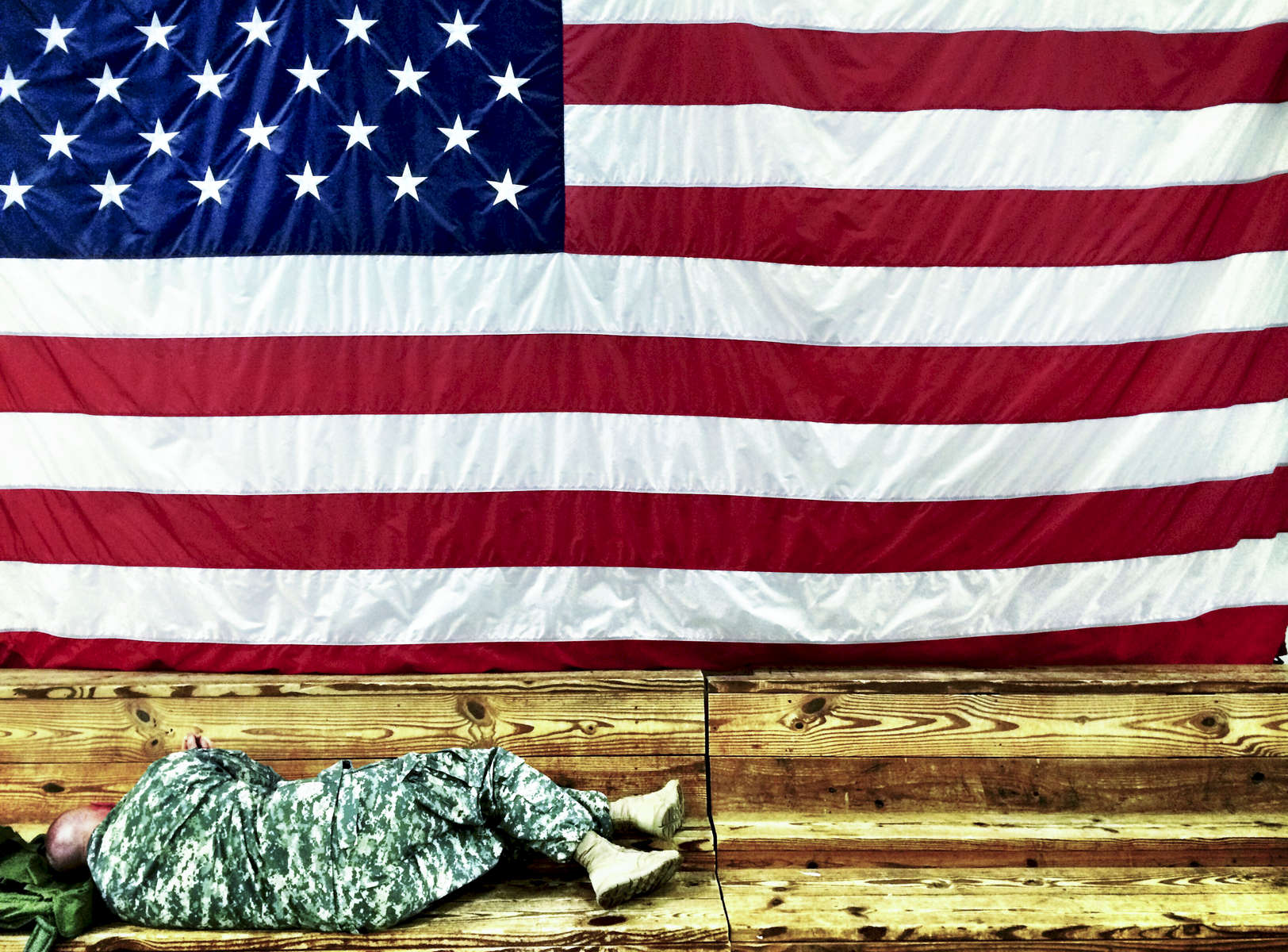 Third Place | Cell Phone Dillon Deaton, UNC Chapel HillSgt. Clifford Hess takes a nap while he waits for the 82nd Sustainment Brigade to arrive at their homecoming celebration on Monday, June 9, 2014.