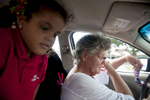 First Place | Feature Photo Story Carolyn Van Houten, UNC Chapel HillMary wipes her eyes in frustration and exhaustion after Nevaeh, 5, climbed into the front of her grandmother\'s moving car.  Nevaeh refused to put her seatbelt on after Mary picked her up from school in Tampa on October 8, 2013.  Mary has found it hard to discipline Nevaeh over the five years that Mary has been raising her since Nevaeh\'s mother was incarcerated.  \{quote}It is not my place to bring up my daughter\'s children,\{quote} Mary said.  \{quote}This is her life.  Those children are her children.  I\'m always going to be there always going to be there for them, but my daughter needs to be the head of her household.  It is not my place anymore.  I want to go out and live some more.\{quote}
