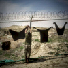 Third Place | Feature Photo StoryAndrew Craft, The Fayetteville ObserverAn Afghan National soldier hangs his clothing up to dry on a fence April 10, 2014, at an ANA artillery school in Kabul, Afghanistan.