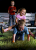 Second Place | Sports Photo StoryJerry Wolford, News & RecordJosey Pulaski, 3, of Trinity, takes a ride on her \{quote}bucking bull,\{quote} Briar Hiatt, 5, of High Point, as the children\'s families talk to friends after the rodeo.