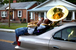 Photographer of the Year Jerry Wolford, News & RecordMarzell Williamson plays his tuba wile riding on the back of a bandmate\'s car as they make their way to Dudley High School\'s band practice after practicing all day in their front yard. For Williamson, success in the marching band, can be a way to access college that otherwise might not exist.