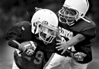 Photographer of the Year Jerry Wolford, News & RecordGlenwood Recreation Center\'s Elijah Allen, 9, grimaces as he tackles running back, Jordan Mitchell, 8, during a preseason scrimmage at practice on Thursday, September 4, 2014.