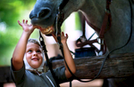 Photographer of the Year Jerry Wolford, News & RecordKali Powers, 6, enjoys pulling the lips of stage horse, Clint, in order to make him, as she says, \{quote}smile.\{quote} Kali performs the role of Jessie Dixon in the outdoor drama, The Sword of Peace on Thursday, August 7, 2014, in Snow Camp, N.C. The play tells the story of pacifist Quakers during the Revolutionary War. The horse carries General Cornwallis onto the stage.