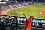 Sports Photographer of the Year Jerry Wolford, News & Record (Greensboro)Canyon Rumley, 7, cheers when a Hoppers\' outfielder throws out a player at first base during the top of the 4th inning (ck. with stats if possible) while eating his popcorn and waiting to catch a foul ball . Canyoon was with his parents, sep-mom Heather Rumley and his father Josh Rumley. The family was in the Web Decisions box behind first base. A collection of firsts from opening night at NewBridge Bank Park on Thursday, April 3, 2014, in Greensboro, N.C.