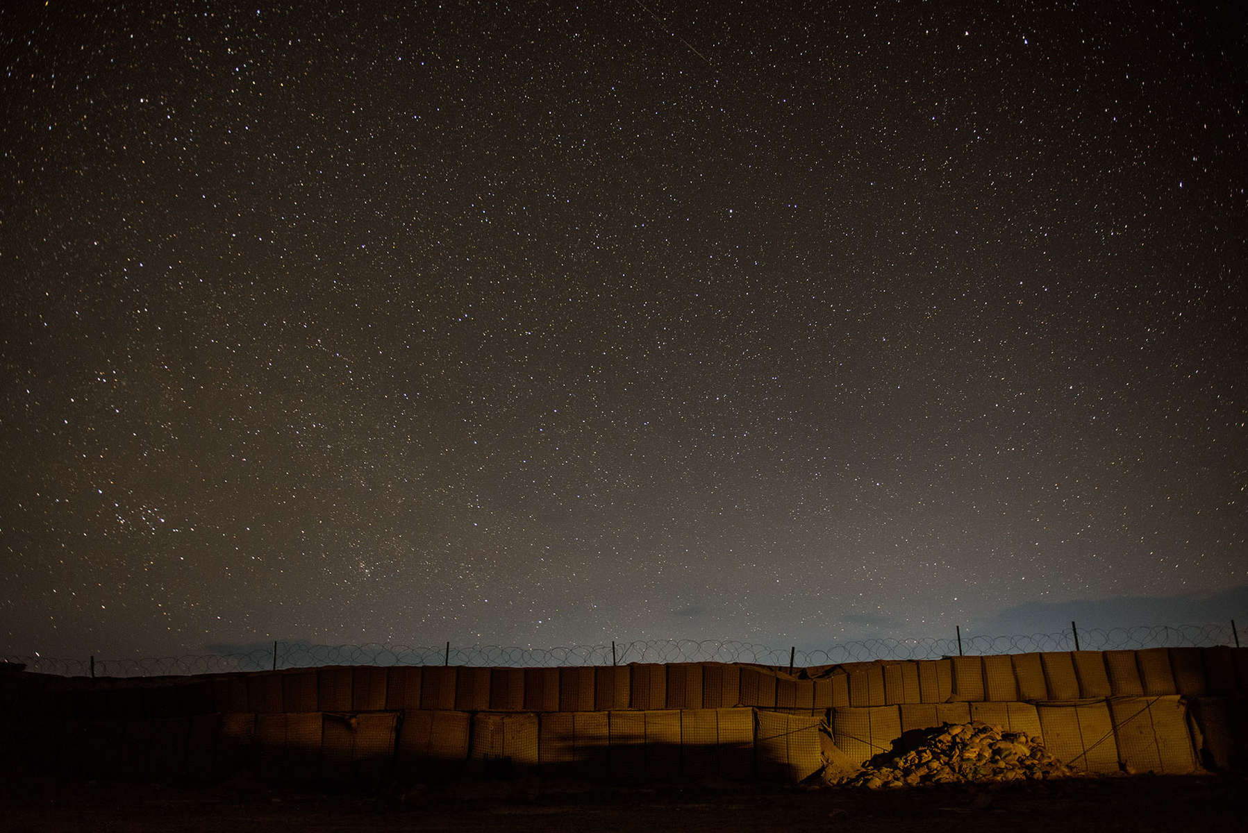 Second Place | Multiple PhotosAndrew Craft, The Fayetteville ObserverThe stars shine brightly above Forward Operating Base Ghazni, which is in almost complete darkness at night. {quote}It's a pretty awesome experience,{quote} First Sgt. Edward King, of D Company, 2nd Battalion, 504th Parachute Infantry Regiment, said. {quote}It was us in the lead. Then them in the lead, but not really. Now they're leading. It's good to see the change that's happened.{quote}Tapping his watch, King said time is running out for U.S. troops in Afghanistan.{quote}They know we're not going to be here to watch them,{quote} he said. {quote}This is their backyard. They want to protect their population, defend their land. We don't have to be standing there alongside them anymore,{quote} he said of the days when soldiers peered over Afghan shoulders to make sure they patrolled correctly. {quote}Those days are long gone.{quote}
