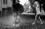 Third Place | FeatureScott Muthersbaugh, Burlington Times-NewsTravis Faulkner, 7, gets a facefull of water as he and his sister Zoey, 6, play in the sprinkler beside their home on Williamson Street in Burlington Tuesday evening.