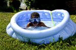 Honorable Mention I FeatureLauren Carroll, Winston-Salem JournalTrequan Butler, 8, celebrates summer break by taking a dip in a kiddie pool in his front yard Monday as his parents, Tanaisha Butler and Rashand Shepherd, watch from the porch.
