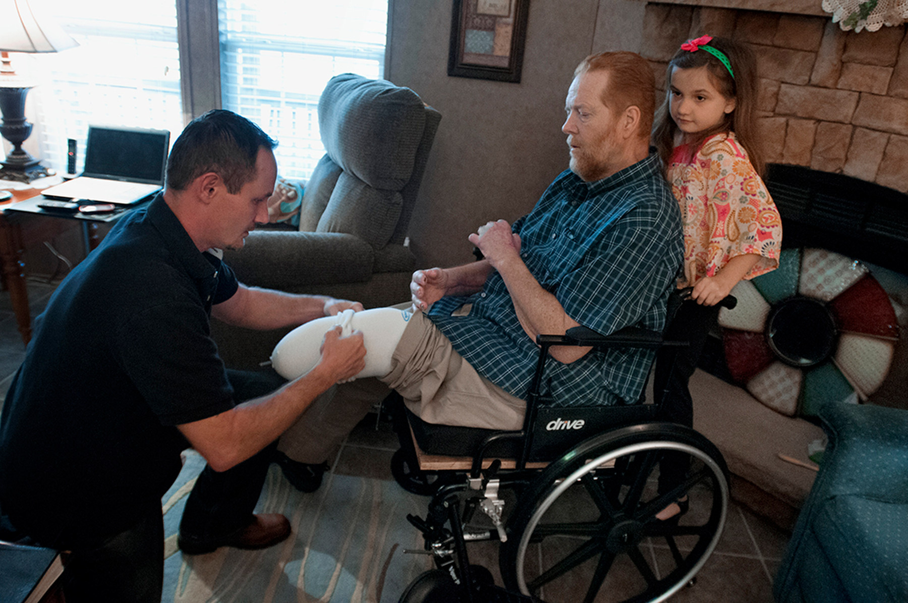 Third Place | Multiple PhotosMike Spencer, The Wilmington Star-NewsMolly Spearman, 7, stands on her fathers wheel chair while Tom Spearman helps his father, Lee, with his with his prosthetic legs at their home in Ingold, N.C., Sunday, March 16, 2014. Lee Spearman was hospitalized in December of 2013 with an infection that was ravaging his body and almost took his life and resulted in having both of his legs amputated below the knee and all the fingers on his left hand.
