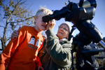 First Place | Multiple PhotosLauren Carroll, Winston-Salem JournalVivian Bast of Winston-Salem helps shield Ben O'Hara's eyes as he looks at the sun safely through a telescope just before a partial solar eclipse Thursday, October 23, 2014. The Forsyth Astronomical Society organized a viewing party at Pilot Mountain State Park.