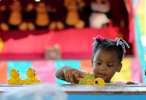 Third Place | Multiple PhotosAdam Jennings, Rocky Mount TelegramAluana Artis, 3, reaches for rubber ducks as part of a game on Monday, Oct. 6, 2014, during the first night of the Rocky Mount Fair.