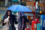 Second Place | FeatureJerry Wolford, News & RecordPat Paz, left, and Myriam Benitez share an umbrella as they support each other against the gusty downtown wind by walking arm in arm along E. McGee St. on Wednesday, November 26, 2014.