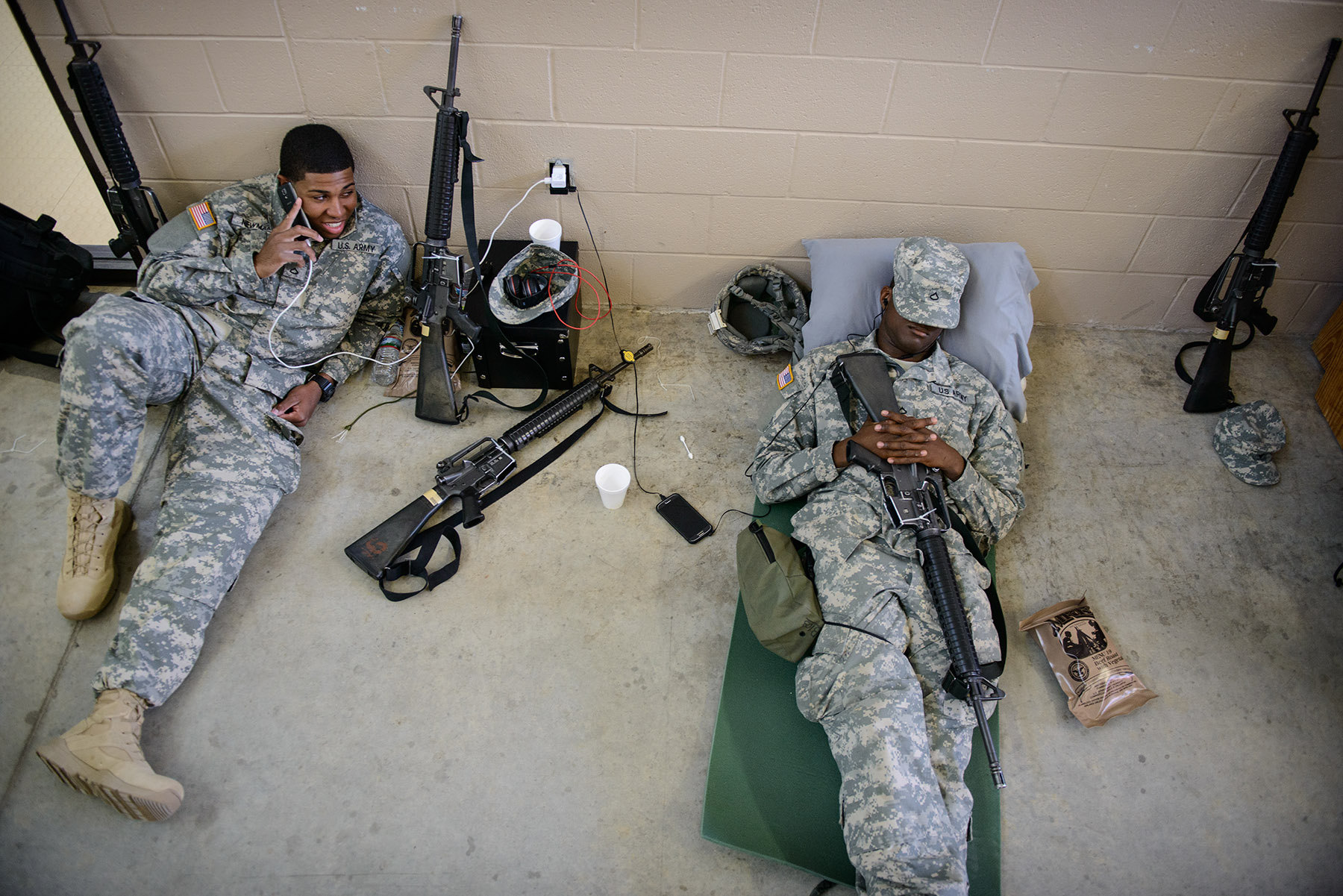 Honorable Mention I FeatureAndrew Craft, The Fayetteville ObserverPfc. Matthew Newman, left, and Pfc. Evan Smith, both of the 50th Signal Battalion, relax as they wait for the flight to West Africa Monday, Nov. 10, 2014, on Fort Bragg. The soldiers are headed to West Africa to help with the containment of the Ebola virus.