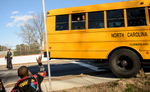 Third Place | Spot NewsAndrew Craft, The Fayetteville ObserverA child waves to a fellow classmate from a school bus that was involved in an accident Friday, Jan. 30, 2014, at Murchison Road and Langdon St. The schoolchildren had to wait on the bus until their parent or guardian showed up to pick them up. The driver of the bus received minor injuries.