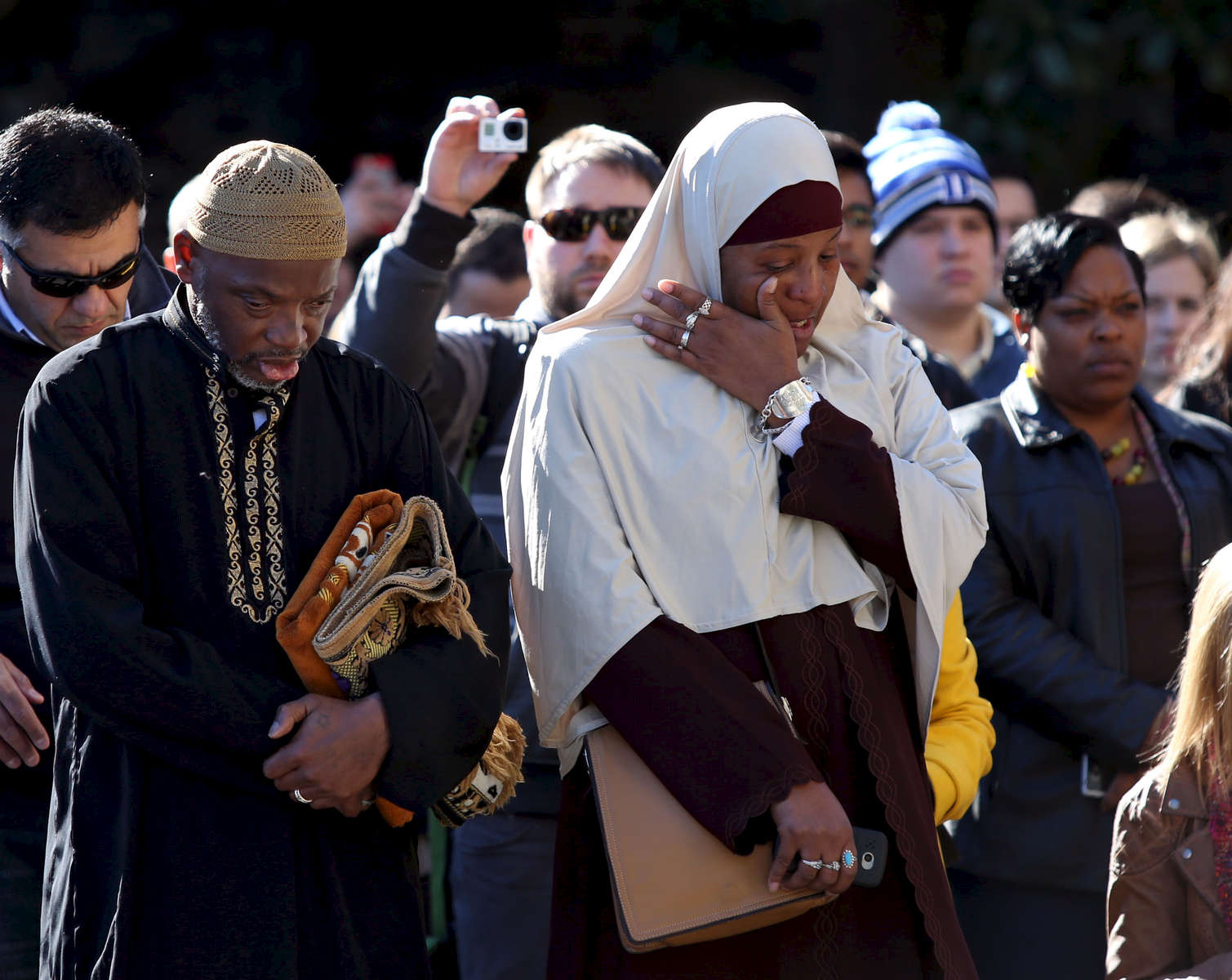 Third Place | General NewsAl Drago, Elon UniversityNija McKay, originally from Brooklyn but now living in Durham, wipes a tear from her face alongside her husband, Aziz, during the call to prayer outside the steps at the Duke Chapel on Friday, January 16, 2015 in Durham, North Carolina. Duke University cited security reasons for reversing their decision to allow the prayer to be played from the chapel bell tower. Instead the prayer was broadcast from a public address system on the steps of the chapel as the member reading the prayer was just behind the chapel door.