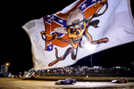 Second Place | Multiple PhotosAndrew Craft, The Fayetteville ObserverA flag flutters in the wind as cars race around the track Saturday, March 28, 2015, at Fayetteville Motor Speedway in Fayetteville, N.C.