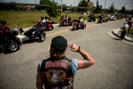 Second Place | General  NewsAndrew Craft, The Fayetteville ObserverBiker Rick McDowell salutes his fellow bikers as they pull into the Airborne and Special Operations Museum parking lot Wednesday, May 20, 2015, during a stop in the Run for the Wall motorcycle ride in Fayetteville, N.C.