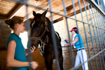 Third Place | Multiple PhotosSara Corce, The PilotFifteen-year-old Emily Crane pets Brio as Diane Ritz brushes him before leaving barn 11 for their scheduled riding time during the Dressage in the Sandhills Horse Show at the Pinehurst Harness Track on Friday, May 8, 2015 in Pinehurst, North Carolina.