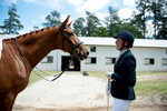 Third Place | Multiple PhotosSara Corce, The PilotLisa Wall, of Apex, laughs as she stands with her horse Baaron Miller Rh outside of barn 11, after riding at their scheduled time, during the Dressage in the Sandhills Horse Show at the Pinehurst Harness Track on Friday, May 8, 2015 in Pinehurst, North Carolina.