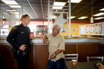 First Place | General NewsAndrew Craft, The Fayetteville ObserverOfficer Scott Bang and Art Laselle talk while having coffee Friday, June 26, 2015, at Hardee\'s during the first \{quote}Coffee With a Cop\{quote} event in Fayetteville, N.C.