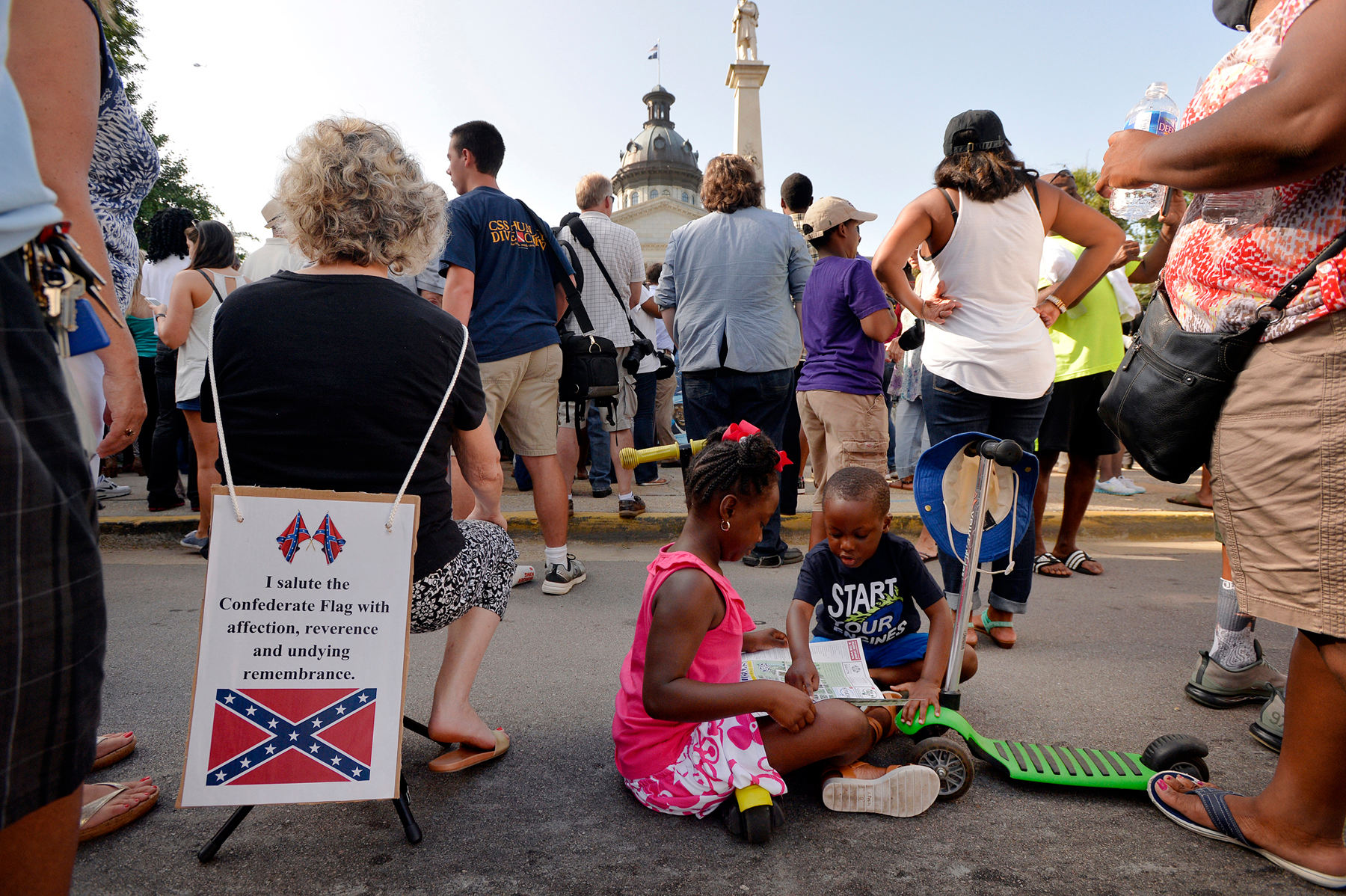 First Place | Multiple PhotosMykal McEldowney, The Greenville NewsFrom left, Charlene Stoll Hale, of Lexington, S.C., wears a banner honor of her Confederate ancestors as Alana Wilson, 7, and Gracen, 5, wait for the removal of the Confederate flag from the Statehouse grounds on Friday, July 10, 2015. {quote}It's so important our children see this moment in South Carolina history,{quote} said Darnnie Carter, mother of the Wilson children.