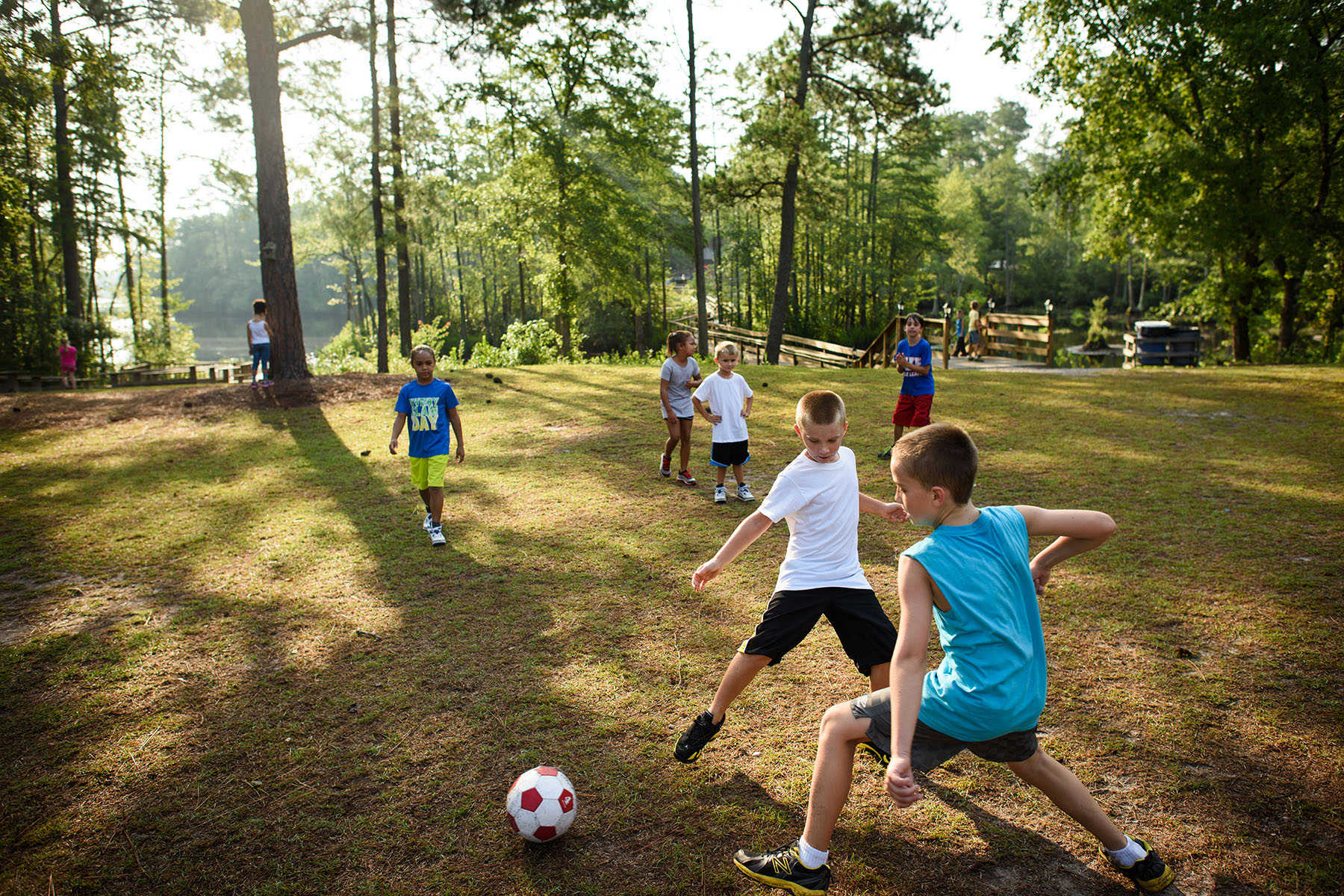 Second Place | Multiple PhotosAndrew Craft, The Fayetteville ObserverCampers kick around a soccer ball Monday, July 20, 2015, at Camp Rockfish.
