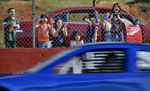 First Place | Multiple PhotosMykal McEldowney, The Greenville NewsKyle Benjamin, a 17-year-old driver from Easley, gets in practice laps at Greenville-Pickens Speedway in Easley on Tuesday, March 24, 2015. Watching and cheering are, from left, Rogelio Mora, 4, Lesly Mora, 8, Julia Roman, 9, Dulce Mora 6, Rosa Roman, 8, and Tiffany Roman, 7.