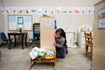 Second Place | Multiple PhotosSara Corce, The PilotJaidy Avila Parra peeks at her class during circle time in the toy kitchen area at HOPE Academy, a recently opened pre-school, on Wednesday, September 16, 2015 in Robbins, North Carolina.