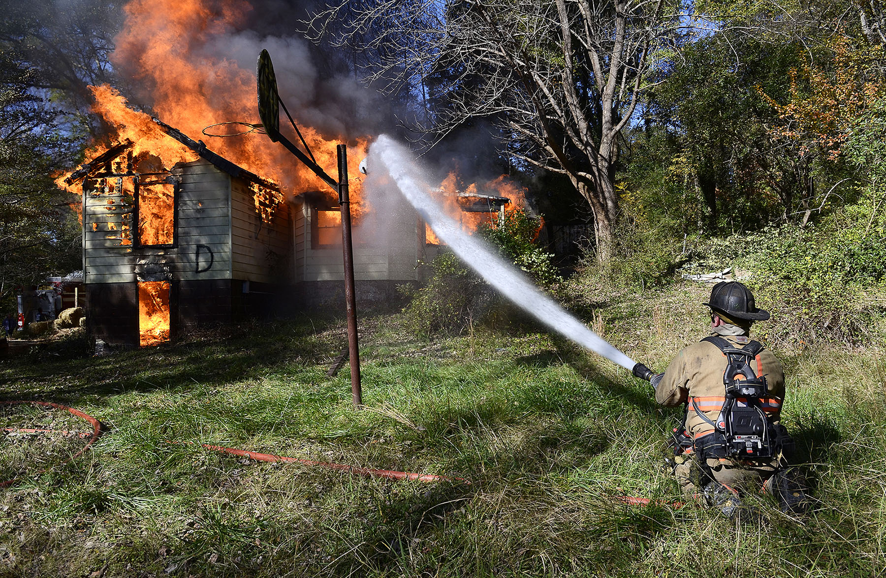 Honorable Mention I General NewsJohn D. Simmons, The Charlotte ObserverBilly Lee, a firefighter with East Gaston VFD, cools down the brush around a practice burn in Mount Holly Saturday. The Mount Holly Fire Department began a practice burn at  8:30 AM  Saturday Nov. 21, 2015 at 114 Price Street. 25 firefighters from Mount Holly, East Gaston VFD and Lucia-Riverbend VFD took part in the training exercise. Mount Holly will conduct a night time practice burn in December at 808 N. Charlotte St.